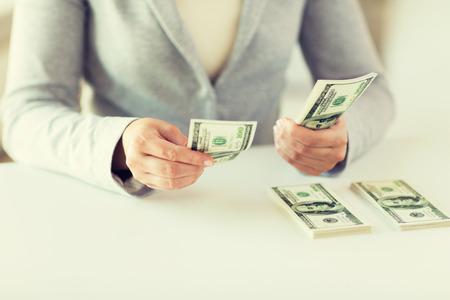 salarios: negocios, las finanzas, el ahorro, la banca y las personas concepto - cerca de las manos de mujer nos cuenta el dinero del dólar Foto de archivo