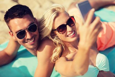 konzepte: Liebe, Reisen, Tourismus, Technologie und Menschen Konzept - lächelnde Paar im Urlaub in der Badebekleidung und Sonnenbrillen und unter selfie mit Smartphone auf Sommerstrand Lizenzfreie Bilder