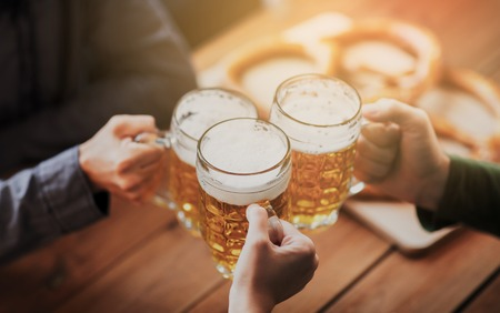 people, leisure and drinks concept - close up of hands clinking beer mugs at bar or pub Foto de archivo