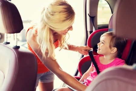 road safety: family, transport, safety, road trip and people concept - happy mother fastening child with car seat belt