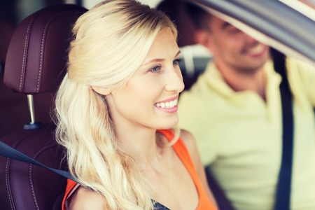 driving car: transport, leisure, road trip and people concept - happy man and woman driving car Stock Photo