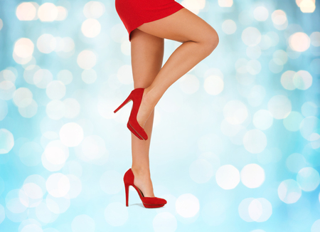 mini: people, fashion and footwear concept - close up of woman legs in red high heeled shoes over blue holidays lights background