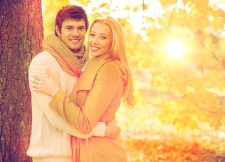 pareja abrazada: días de fiesta, amor, los viajes, el turismo, la relación y el concepto de citas - pareja romántica en el parque del otoño Foto de archivo