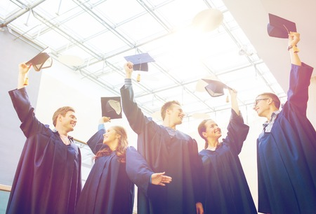 academic robe: education, graduation and people concept - group of happy students or bachelors in gowns waving mortarboards at school Stock Photo