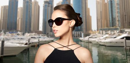 eyewear fashion: accessories, eyewear, fashion, people and luxury concept - beautiful young woman in elegant black sunglasses over dubai city port background
