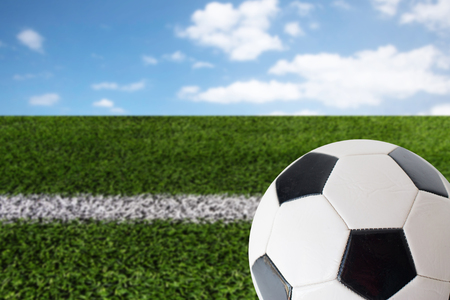 blue ball: sport, football and sports equipment concept - close up of soccer ball over playing field and blue sky background