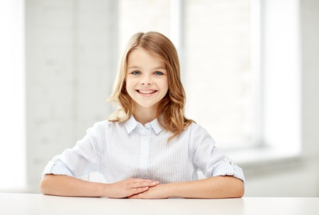 school class: education, elementary school, learning, children and people concept - happy smiling girl sitting at table Stock Photo