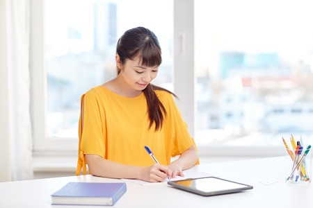 happy asian people: people, education, high school and learning concept - happy asian young woman student with tablet pc computer, book and notepad writing at home