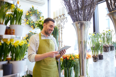 Online Business: people, business, technology, sale and floristry and concept - happy smiling florist man with tablet pc computer at flower shop