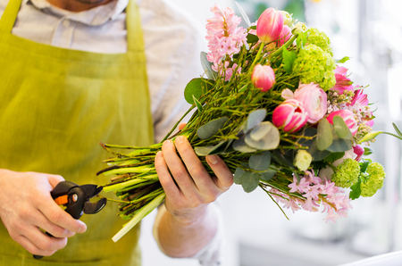 cropping: people, business, sale and floristry concept - close up of florist man making bunch and cropping stems by pruner at flower shop