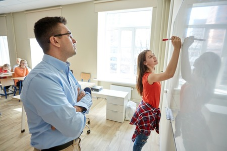 middle class: education, school, learning and people concept - student girl writing something on blank white board and teacher in classroom Stock Photo