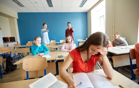 education, bullying, conflict, social relations and people concept - students teasing and judging girl classmate behind her back at school Stock Photo