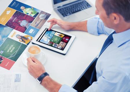 negocio, personas, medios de comunicación y la tecnología concepto - hombre de negocios con PC de la tableta de lectura de noticias de Internet y el consumo de café en la oficina Foto de archivo
