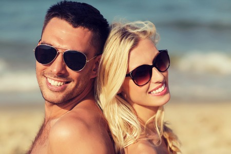 romantic beach: love, travel, tourism, summer and people concept - smiling couple on vacation in swimwear sitting on beach back to back Stock Photo