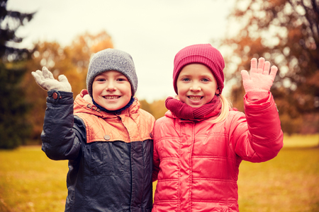 childhood, leisure, friendship, autumn and people concept - happy little girl and boy waving hands in park Stock Photo