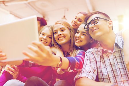 taking video: education, high school, technology and people concept - group of smiling students with tablet pc computer taking photo or video indoors Stock Photo