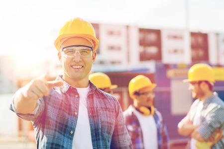 ビジネス、建築、建設、ジェスチャー、人々 の概念 - hardhats を屋外に指を指して笑って建設業者のグループ