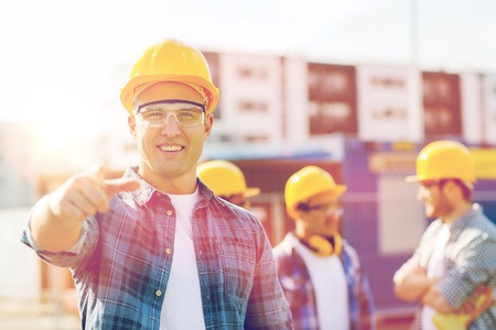 het bedrijfsleven, de bouw, bouw, gebaar en mensen concept - groep lachende bouwers in bouwvakkers die vinger op u buiten Stockfoto