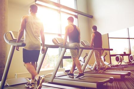 hombres haciendo ejercicio: deporte, fitness, estilo de vida, la tecnología y el concepto de la gente - los hombres que ejercitan en la cinta en el gimnasio