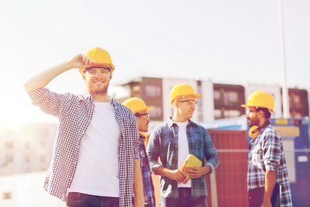 many people: business, building, construction and people concept - group of smiling builders in hardhats outdoors Stock Photo