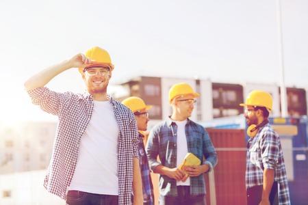mucha gente: negocio, construcción, construcción y concepto de la gente - grupo de constructores sonrientes en sombreros duros al aire libre