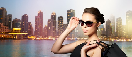 sale, tour, fashion, people and luxury concept - happy beautiful young woman in black sunglasses with shopping bags over dubai city night lights background