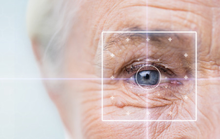 age, vision, surgery, eyesight and people concept - close up of senior woman face and eye with laser light Stockfoto