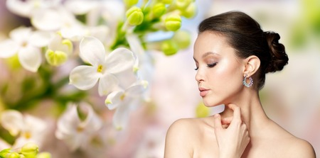 green gemstone: beauty, jewelry, accessories, people and luxury concept - close up of beautiful asian woman face with earring over natural spring lilac blossom background