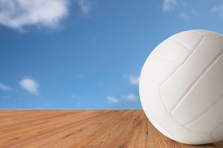 objects equipment: sport, fitness, game, sports equipment and objects concept - close up of volleyball ball over blue sky and wooden floor background Stock Photo