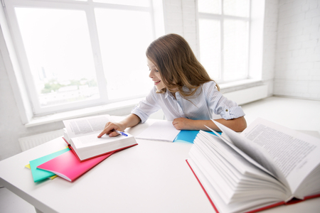 learning by doing: education, elementary school, learning and people concept - happy smiling girl with books and notebook doing homework