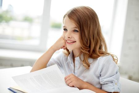 niños estudiando: la educación, la gente, los niños y el aprendizaje de conceptos - libro de lectura de la niña feliz estudiante en la escuela Foto de archivo