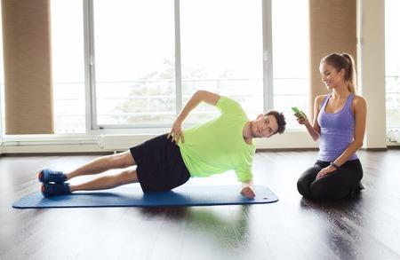 fitness hombres: fitness, deporte, tecnología y personas concepto - el hombre y la mujer con el teléfono inteligente hacer ejercicio tabla lateral en la estera en el gimnasio