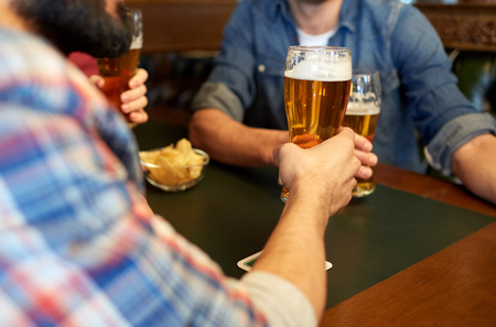 people, leisure, drinks and celebration concept - happy male friends drinking beer at bar or pub