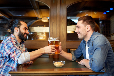 people, leisure, friendship and party concept - happy male friends drinking draft beer at bar or pub and clinking glasses Stock Photo