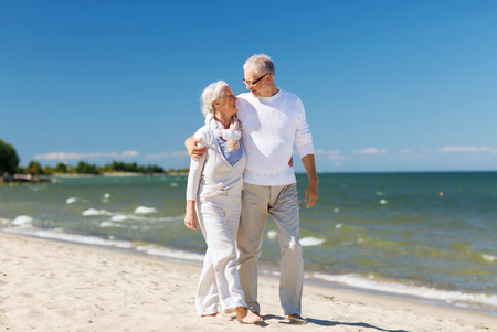 old people walking: family, age, travel, tourism and people concept - happy senior couple hugging on summer beach
