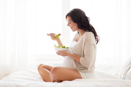 buena salud: el embarazo, la alimentación saludable y el concepto de personas - mujer embarazada feliz comiendo una ensalada de verduras para el desayuno en su casa