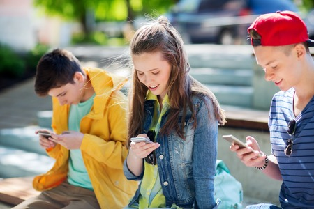 mobile phones: technology, internet addiction and people concept - happy teenage friends with smartphones outdoors