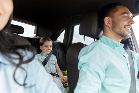 road safety: family, transport, safety, road trip and people concept - happy man and woman with little child driving in car