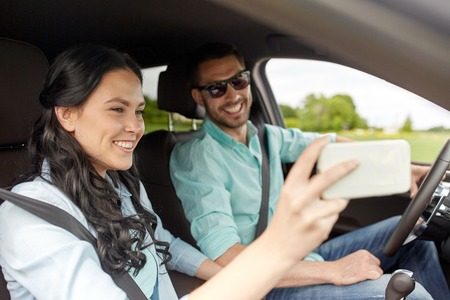 Viaje por carretera, ocio, pareja, la tecnología y el concepto de la gente - hombre feliz y mujer conduciendo en el coche y tomando autofoto con smartphone Foto de archivo - 63832813