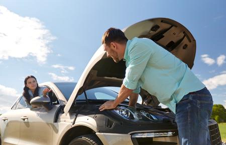 road trip, transport, reizen en mensen concept - familie paar met open kap van de gebroken auto op het platteland