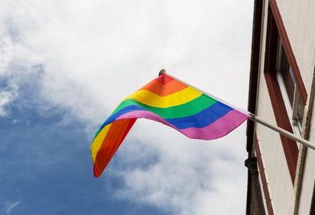 homosexuality: homosexuality, symbolic and gay pride concept - close up of rainbow flag waving on building