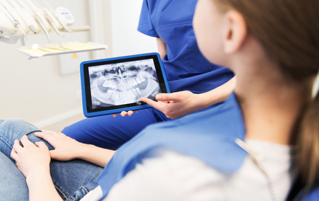health technology: people, medicine, stomatology, technology and health care concept - close up of female dentist showing teeth x-ray on tablet pc computer screen to patient girl at dental clinic office