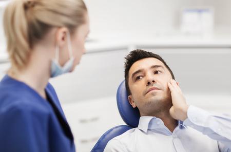 mensen, geneeskunde, tandheelkunde en zorgconcept - mannelijke patiënt met tandpijn klagen bij vrouwelijke tandarts op tandheelkundige kliniek kantoor