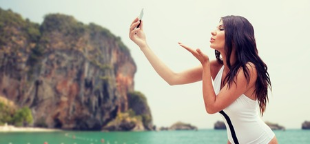 bali beach: summer, travel, technology and people concept - sexy young woman taking selfie with smartphone and sending blow kiss over rock on bali beach background Stock Photo