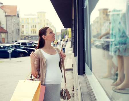 expectation: pregnancy, motherhood, people and expectation concept - happy smiling pregnant woman with shopping bags at city street Stock Photo