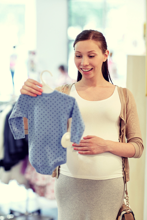 choosing clothes: pregnancy, people, sale and expectation concept - happy pregnant woman shopping and buying baby bodysuit at children clothing store