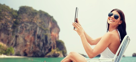 bali beach: summer vacation, tourism, travel, holidays and people concept - smiling young woman with tablet pc computer sunbathing in lounge or folding chair over rock on bali beach background Stock Photo