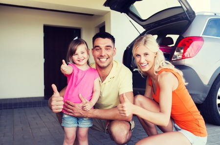 hatchback: transport, leisure, road trip and people concept - happy  family with little girl and hatchback car showing thumbs up at home parking space