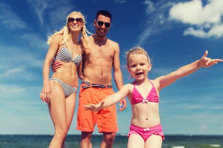 resort life: family, childhood, travel and people concept - close up of happy man, woman and little girl having fun on summer beach Stock Photo