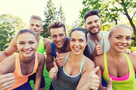 fitness, sport, vriendschap en gezonde levensstijl concept - groep van gelukkige tiener vrienden tonen duimen omhoog in openlucht